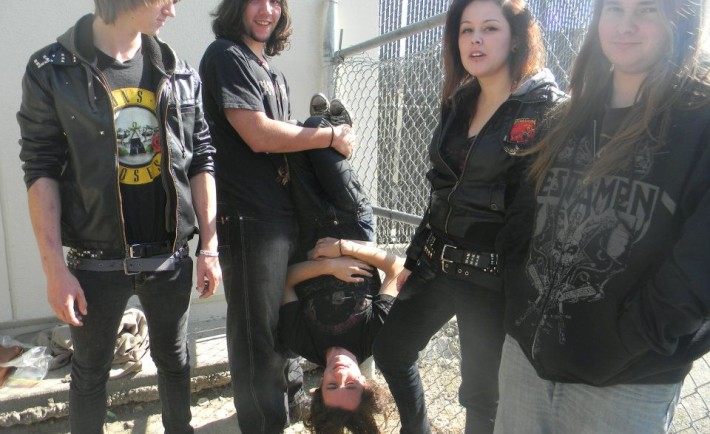Left to right: Kyle Wallinger (drums), Adam McDaniel (guitar), Jake Quarle (upside-down)(vocals), Alyssa Porras (bass), and Jared Charles (guitar).